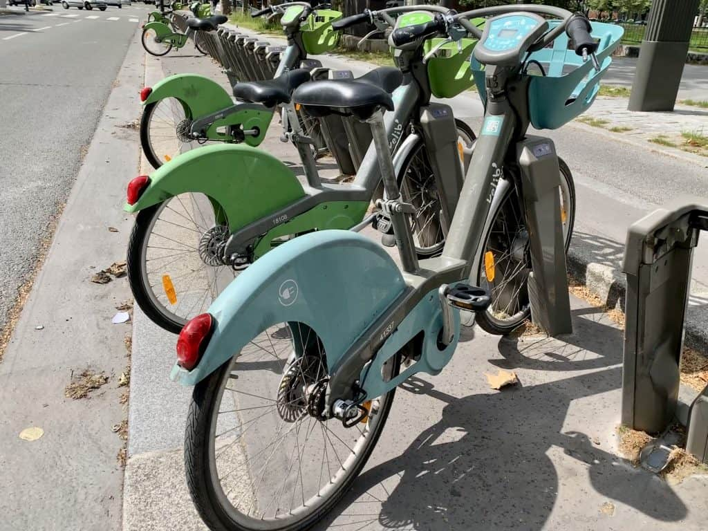 A Vélib station in Paris - the blue bikes are e-bikes, the green ones normal push bikes. how to use velib is very easy